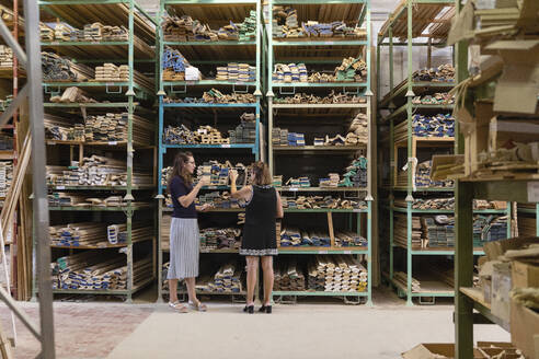 Woman choosing wood while standing at warehouse of factory - EIF00287