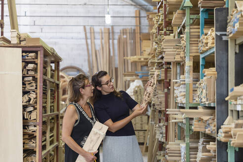 Female employee selecting ornate wood while standing in warehouse at factory - EIF00290