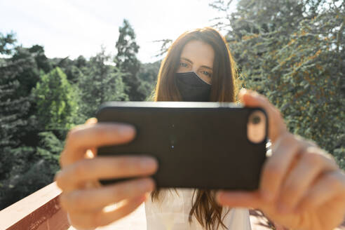 Young woman taking selfie on smart phone wearing protective face mask on sunny day - AFVF07319