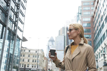 Businesswoman with coffee cup looking away while standing in city - PMF01330
