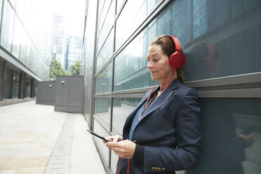 Businesswoman listening music while leaning on building in city - PMF01339