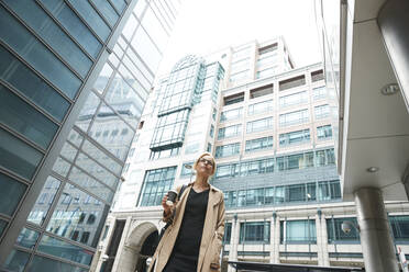 Businesswoman with coffee cup and hand in pocket standing in city - PMF01345