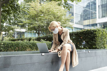 Businesswoman wearing face mask working on laptop in city - PMF01348