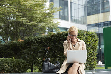 Businesswoman talking on mobile phone while working on laptop at office park - PMF01351