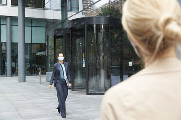 Colleague waiting for woman walking with laptop against office building - PMF01369