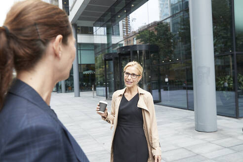 Smiling colleague talking to businesswoman while standing in city - PMF01375