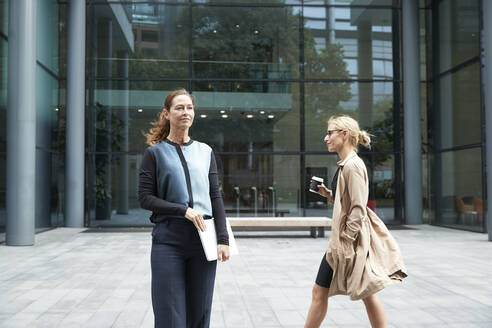 Mature woman standing and holding laptop with colleague walking in background against office building - PMF01381