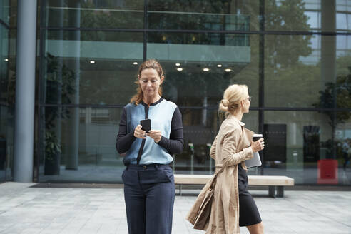 Businesswoman using mobile phone with colleague leaving after work in background - PMF01384