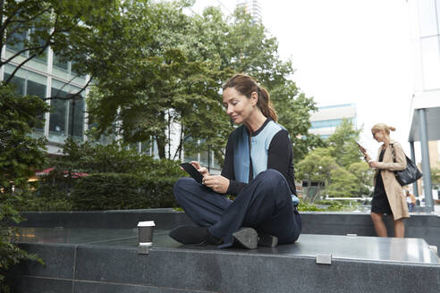 Businesswoman using mobile phone while sitting on bench with colleague standing in background at office park - PMF01387