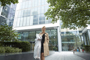 Businesswoman holding shopping clothes while standing at office park - PMF01390