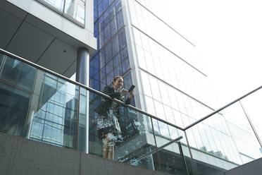 Businesswoman using smart phone while leaning on railing against modern office building - PMF01405