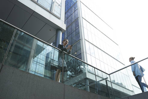 Businesswoman using mobile phone while standing by woman on railing in city - PMF01408