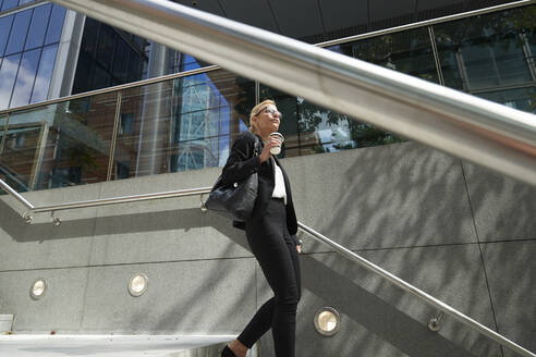 Mature woman with coffee cup walking on staircase against building exterior - PMF01411
