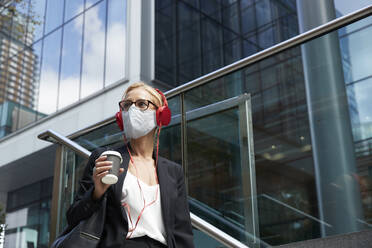 Businesswoman with coffee cup listening music while standing against building - PMF01414
