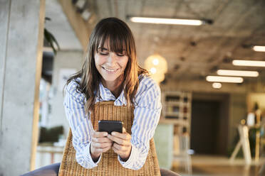 Mature woman smiling while text messaging on smart phone sitting at home - FMKF06547