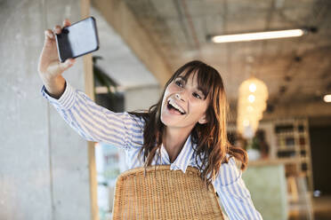 Happy mature woman with mouth open taking selfie on smart phone while sitting at home - FMKF06550