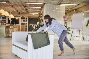 Smiling mature woman pushing sofa at home - FMKF06556