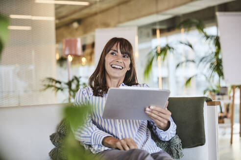 Happy woman using digital tablet while sitting at modern home - FMKF06561