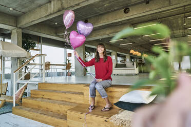 Businesswoman holding balloons while sitting on stairs in loft office - FMKF06606