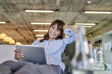Smiling woman with hand in hands using digital tablet while sitting on sofa at home - FMKF06627