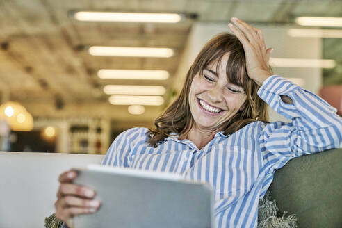 Woman with head in hand laughing while using digital tablet at home - FMKF06630