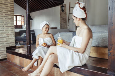 Smiling woman and girl in towel having fruit and juice while sitting at home - JSMF01861