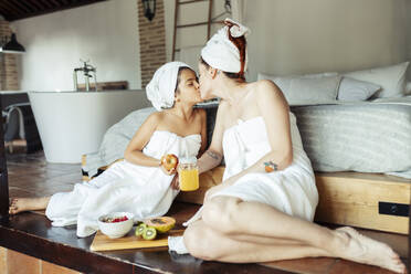 Mother and daughter in towel kissing while sitting in bedroom at home - JSMF01864