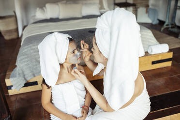 Mother applying facial cream to daughter while sitting at home - JSMF01870
