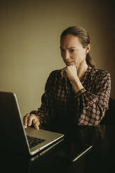 Businesswoman working on laptop while sitting in office - DMGF00181