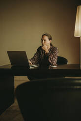 Thoughtful woman working on laptop while sitting in office - DMGF00184