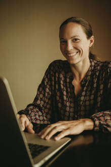 Smiling businesswoman working on laptop while sitting in office - DMGF00187