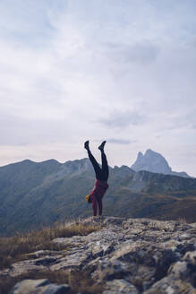 Young man doing handstand on mountain around Ibones of Anayet - RSGF00362
