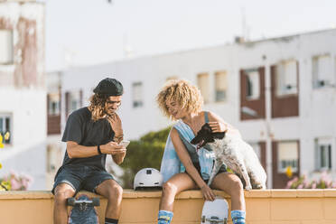 Friends using mobile phone while sitting with dog on retaining wall in city - DAMF00556