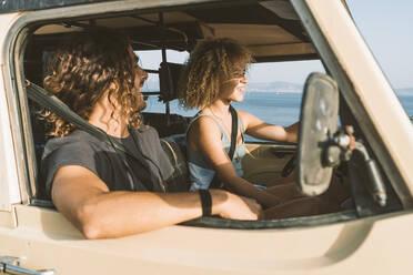 Man looking at woman driving car at beach - DAMF00559