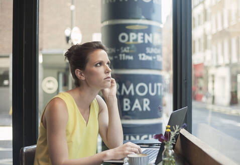 Thoughtful young businesswoman with laptop at coffee shop - AJOF00258