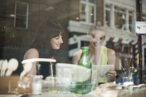 Smiling businesswomen discussing over document during meeting in coffee shop seen through window glass - AJOF00270