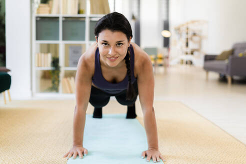 Young woman doing push ups at home - GIOF09151