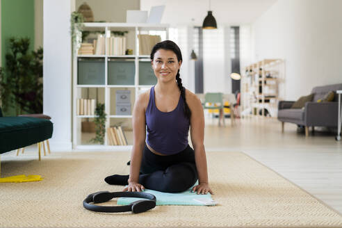 Young woman with pilates ring sitting on exercise mat at home - GIOF09166