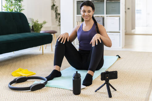 Smiling young woman video recording while sitting on exercise mat at home - GIOF09175