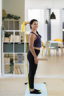 Smiling young woman stretching with resistance band standing at home - GIOF09181