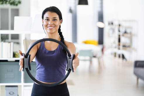 Smiling young female doing pilates ring exercise while standing at home - GIOF09184