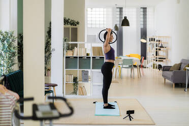 Female influencer exercising with pilates ring and video recording on camera at home - GIOF09187