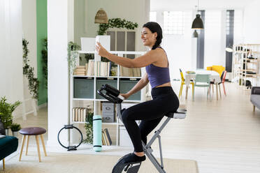 Young woman taking selfie while sitting on exercise bike at home - GIOF09190