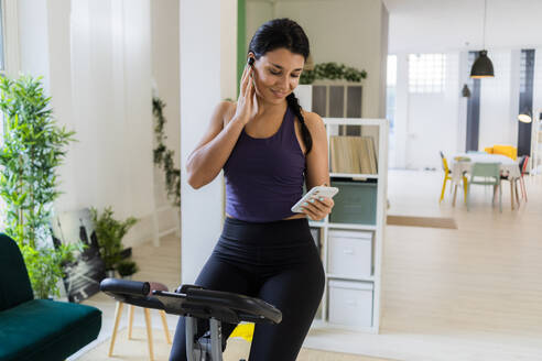 Smiling athlete listening music through bluetooth while sitting on exercise bike at home - GIOF09196