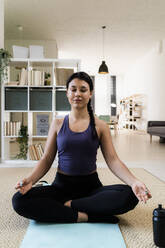 Young woman meditating while sitting on exercise mat at home - GIOF09208