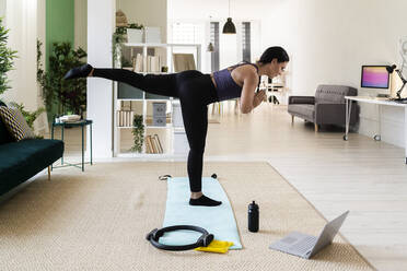 Young female athlete with one leg up standing on exercise mat at home - GIOF09211