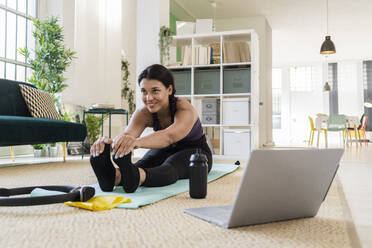 Smiling female athlete looking away while doing stretching exercise sitting at home - GIOF09214