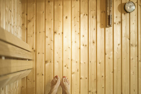Legs of woman against wooden wall in sauna - CHPF00685