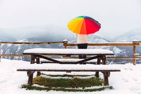 Back view of anonymous person standing under colorful umbrella and enjoying amazing view of Pyrenees mountain ridge covered with snow in winter - ADSF16610