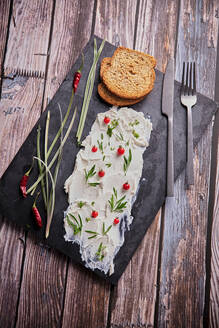 From above of tasty cream cheese and pieces of fresh bread arranged with various herbs on slate board on wooden table - ADSF16619